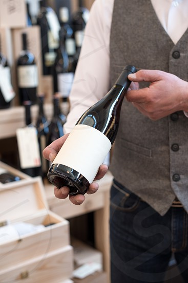 Seller holding red wine bottle photo