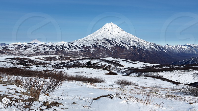 Kamchatka Peninsula winter panorama mountainous landscape: beautiful view of snowy cone of Vilyuchinsky Volcano. Eurasia Russian Far East Kamchatka Region. photo