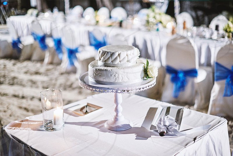 Selective focus on two layers wedding cake on the table with knife for cake cutting and wedding dinner table in background photo