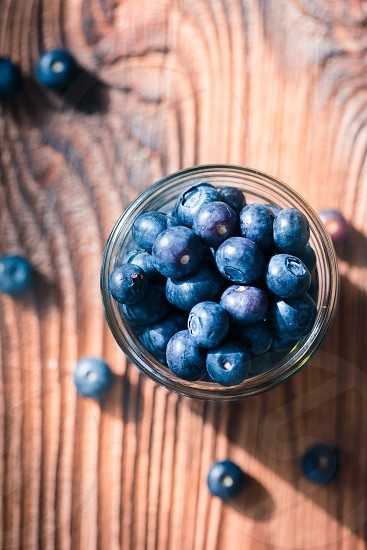 Freshly gathered blueberries put into jar. Some fruits freely  scattered on old wooden table. Shot from above photo