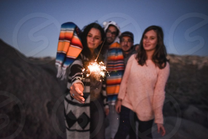 two men and two women watching sparkler in tilt shift lens photo