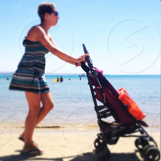 woman pushing a stroller on the beach photo