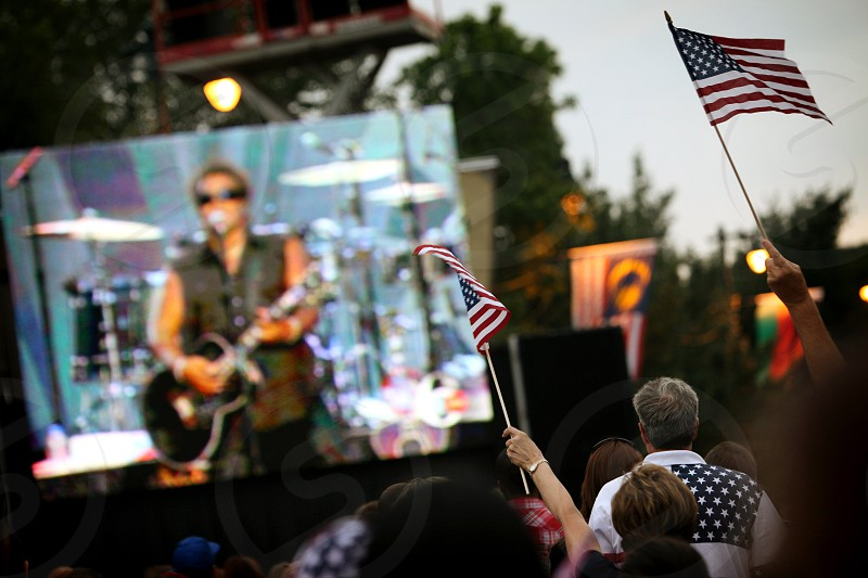 A video monitor screen projection LED display projects a rock and roll star singing and playing a guitar as fans in the crowd wave American flags overhead. photo