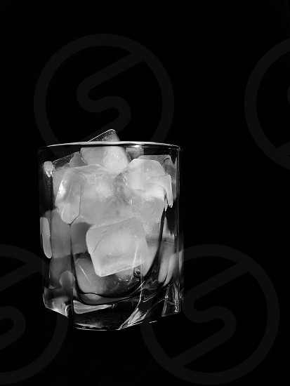 grayscale photo of clear round base rock glass with ice cubes photo