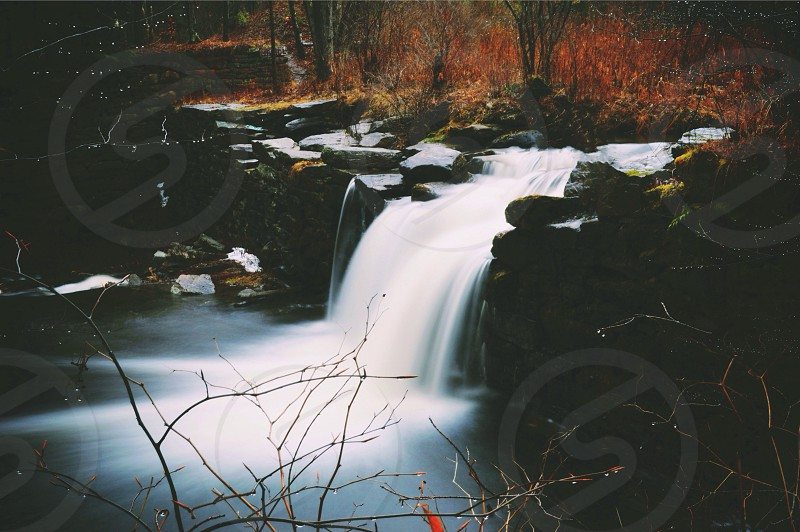 water fall over brown rocks photo