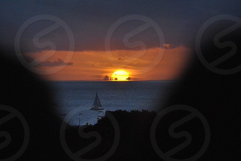 sun dipping below waterline at night with sailboat in foreground photo
