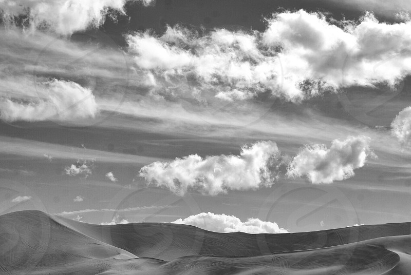 Desert sand dunes and clouds in black and white photo