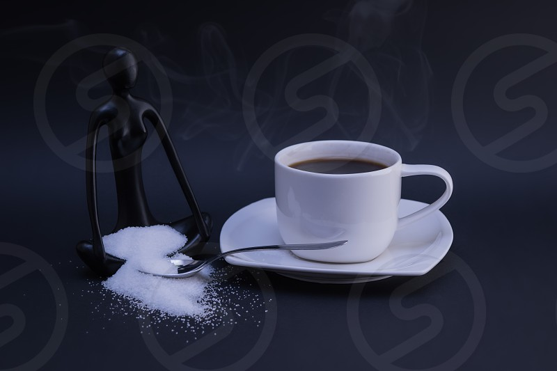 Coffee drink lifestyle sugar concentration  meditating statue spoon fresh morning energy drink espresso steam dark table  photo