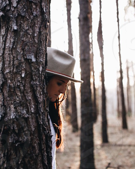 woman wearing white fedora hat standing behind the tree during daytime photo