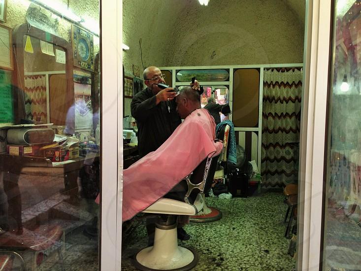 man wearing pink barber robe getting hair cut photo