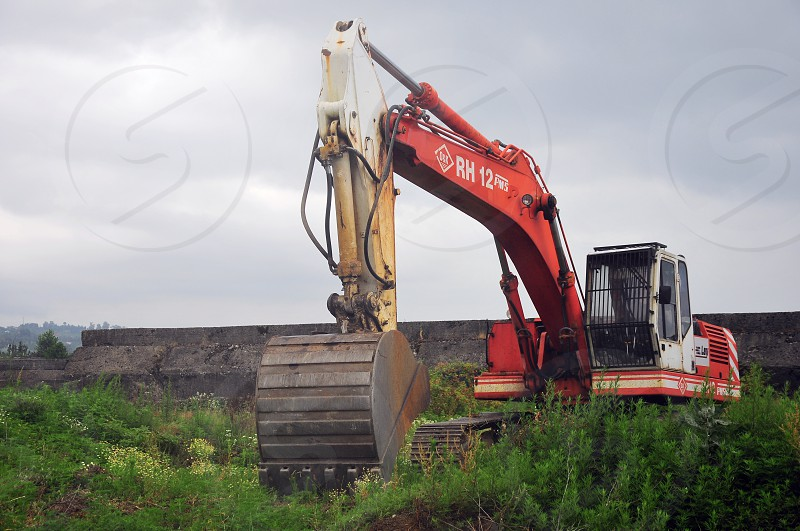 red and yellow metal loader machine on green landscape under grey cloudy sky photo