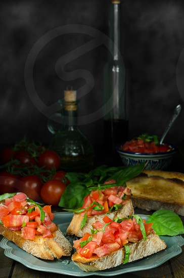 Bruschetta with tomatoes and basil on old plate with ingredients on dark background photo