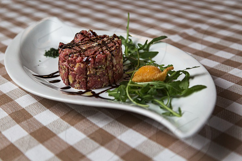 The tartare is a dish of French origin made from beef or horse meat which is served raw and cut with a knife into very small pieces. served with green rocket leaves soft focus photo