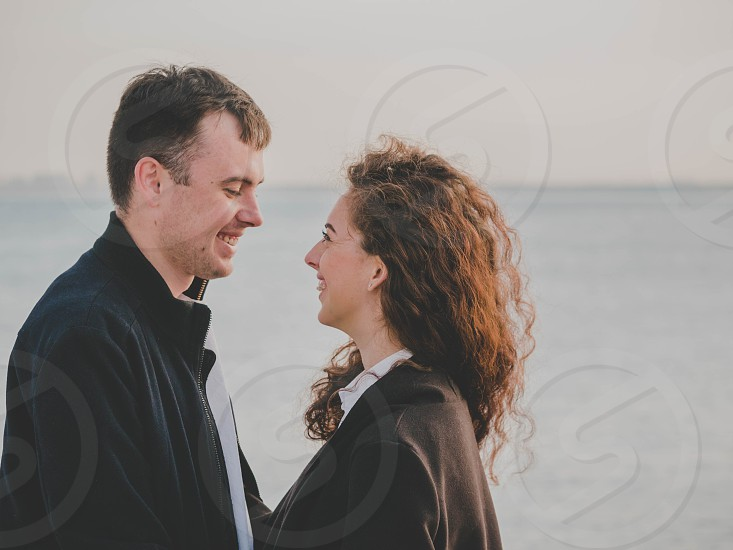 Young romantic couple in trendy wear on date enjoying moment of closeness on sea or ocean background. Woman with curly hair smiling to her man. Romantic concept. photo