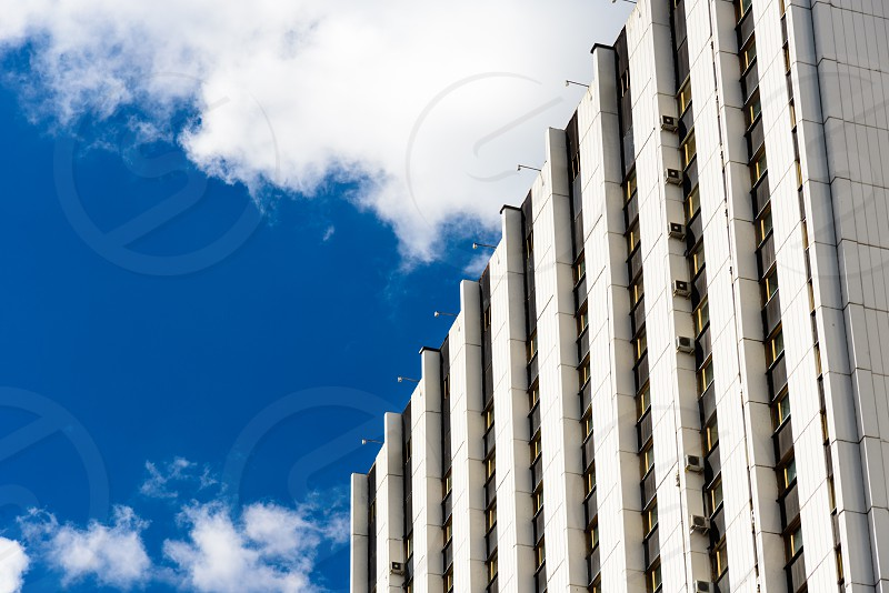 Facade of a building in Moscow against blue sky with some clouds photo