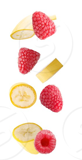 Isolated flying fruits. Falling banana and raspberry fruits isolated on white background with clipping path as package design element and advertising. photo