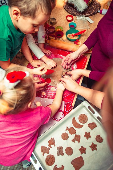 Baking Christmas cookies. Christmas gingerbread cookies in many shapes decorated with colorful frosting sprinkle icing chocolate coating toppers put on table. Baking traditional cookies. Family celebrating Christmas. Baking at home. Baked sweet cookies. Coating with frostings. Colouring cookies. Decorating baked cookies. Decoration and design of food. Flat top-down composition. Sweet dessert food. Putting a frost frosting gingerbread. Shot from above photo
