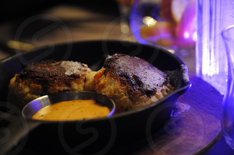 Two crab cakes and remoulade sauce in a cast iron skillet on a table with a purple light (example from Bourbon Street Steakhouse West Memphis AR) Arkansas Food photo