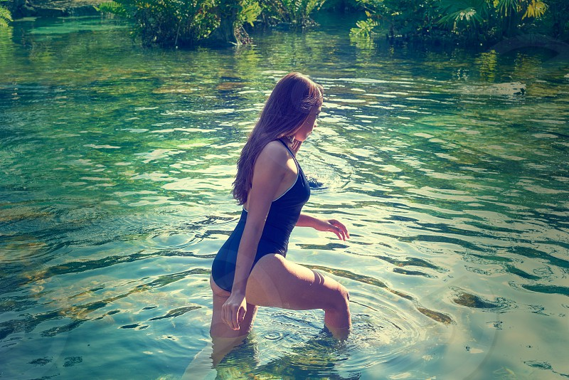 Beautiful teen girl in cenote of Riviera Maya with swimsuit photo