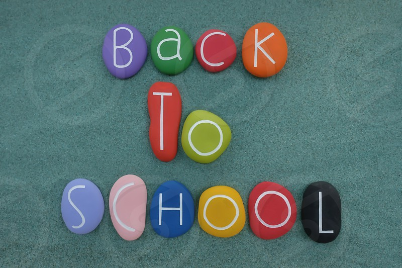 Back to School text composed with multi colored and carved stones over green sand photo