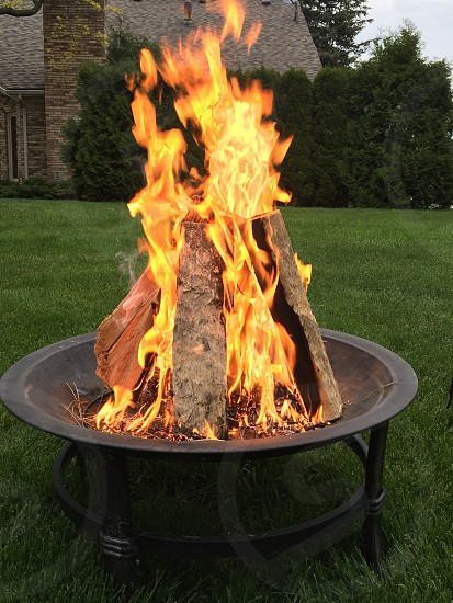 firewood on fire on round black firepit photo