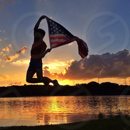 man holding usa country flag jumping over the sea and the mountain at sunset photo