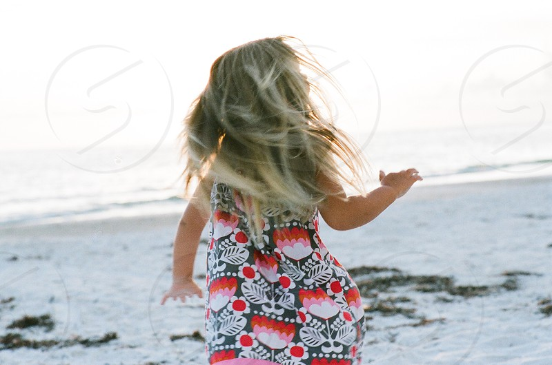 Beach little girl fun playing twirling sun ocean photo