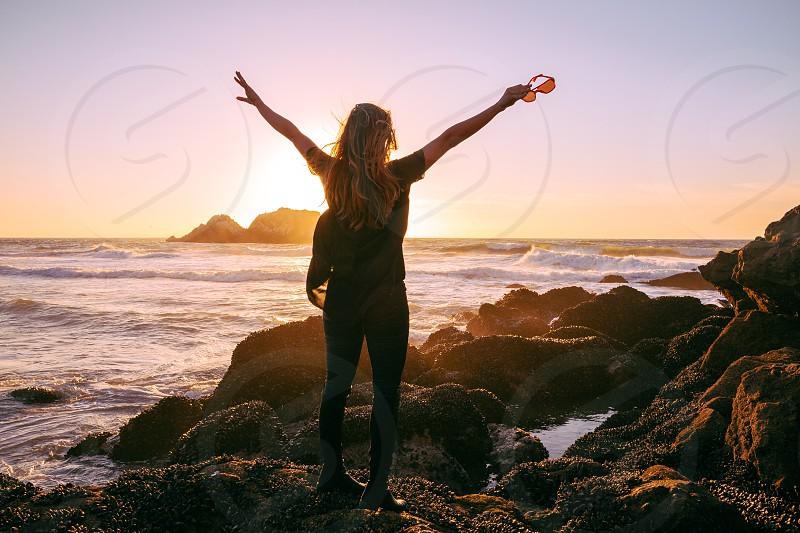 woman in brown shirt standing on seashore photo