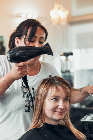 Hairdresser styling dyeing combing womans hair. Young woman working as a hairdresser in hair salon. Real people authentic situations photo
