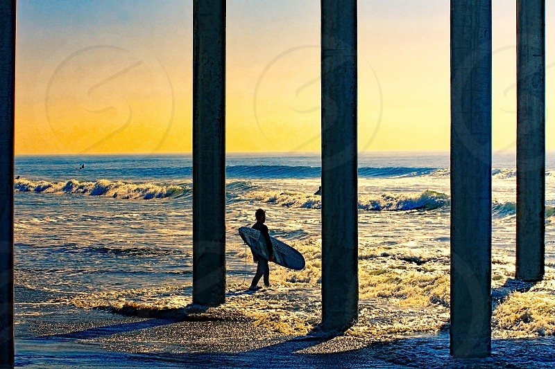 In silhouette a surfer holding his surfboard walks into the ocean between the beams of a pier above him. photo