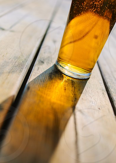 Light refracted through a pint of lager onto a wooden table in a pub beer garden photo