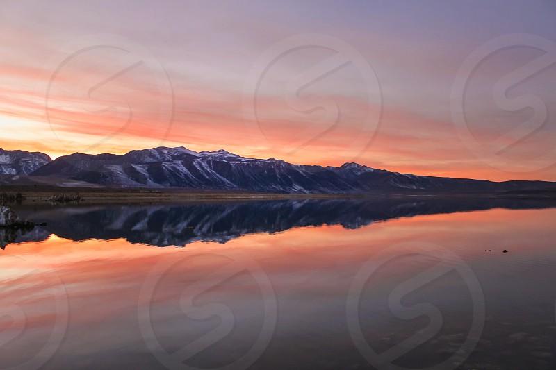 mountain beside body of water under orange sky during daytime photo