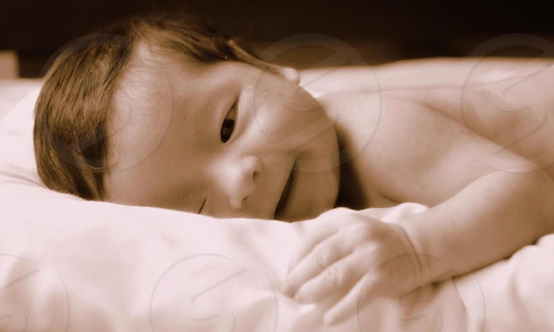 baby sleeping on white textile photo