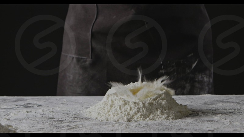 Woman in black apron and dropping fresh yolk into heap of flour. Step by step process of preparation nature dough for homemade pasta. Slow motion Full HD video 240fps 1080p. photo