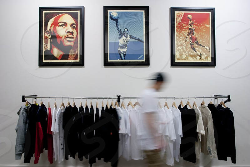 3 black framed athlete portraits on wall above shirts hanging on rack photo