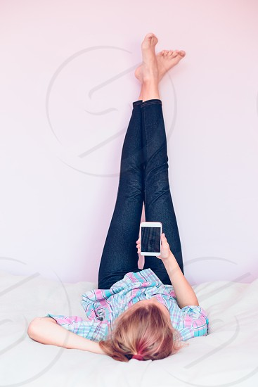 Young girl wearing jeans using mobile phone lying on bed with legs up spending time alone reading a ebook photo