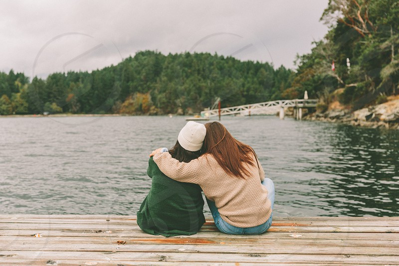 Two women sitting together at the end of a dock.  photo
