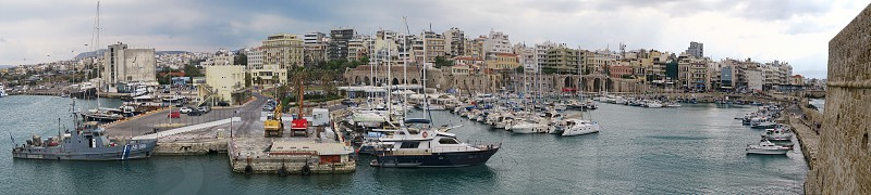 Iraklion Crete / GREECE May 17 2017: Cityscape of Iraklion capital of Crete Isle (Greece). Sailing boats and ferries in harbor. In background the old town part of Iraklion.  panorama of 5 images. photo