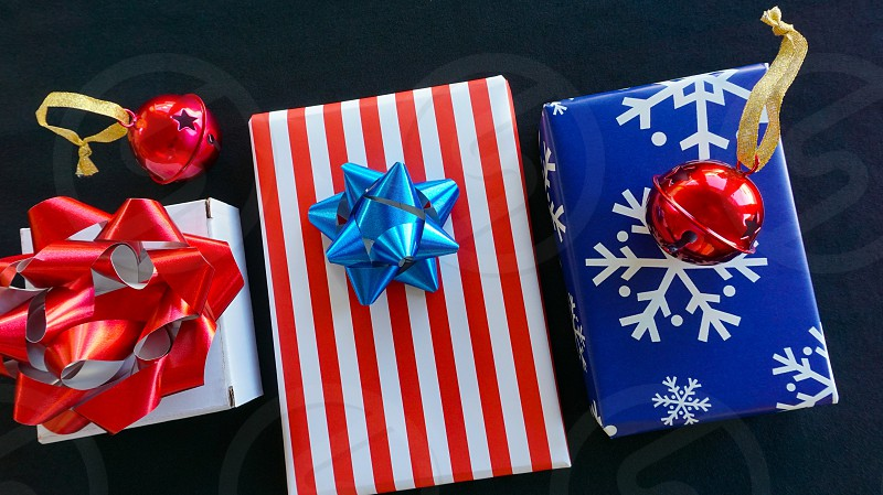 Trio of gifts for the Christmas holidays in red white and blue wrapping bows photo