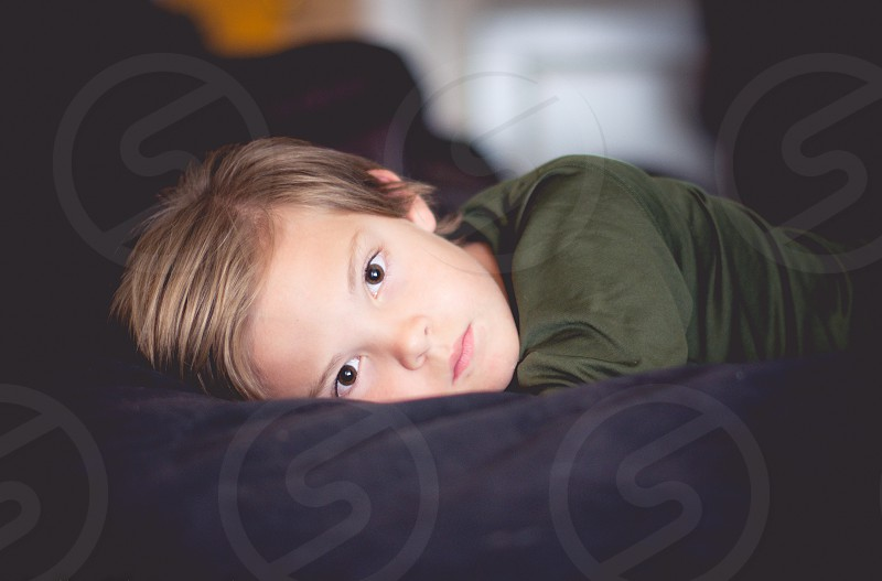 boy in green shirt leaning on bed photo