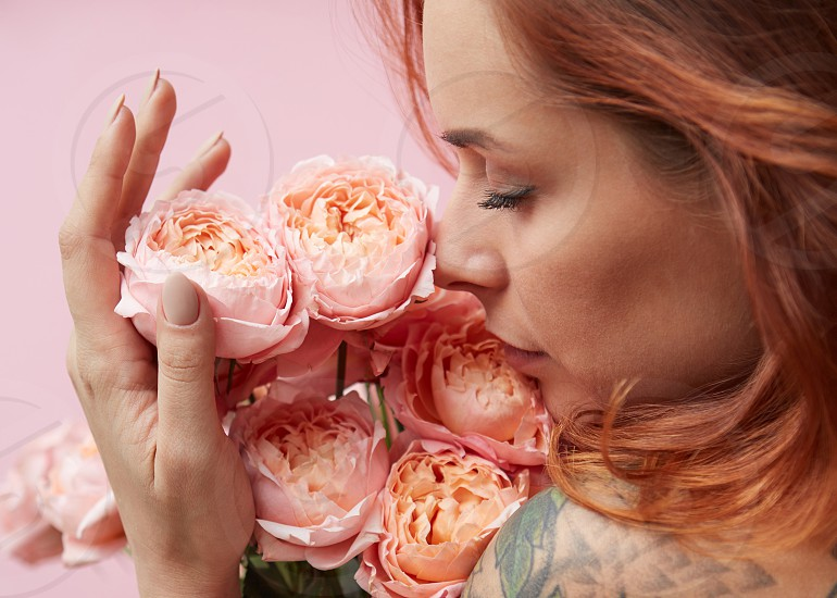 Red-haired cute woman is sniffing a bouquet of pink Buttercup Asian on a pink background. Mother's Day photo