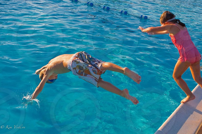 boy wearing blue floral shorts diving on the body of water during daytime photo