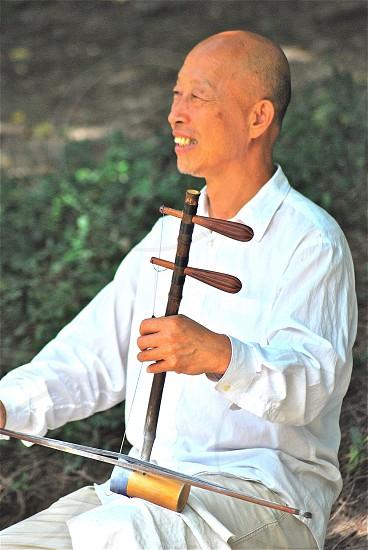 man wearing white dress shirt playing musical instrument photo