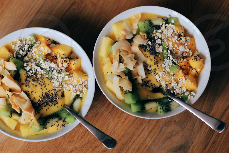 two bowls of fruit salad with sprinkled oats photo