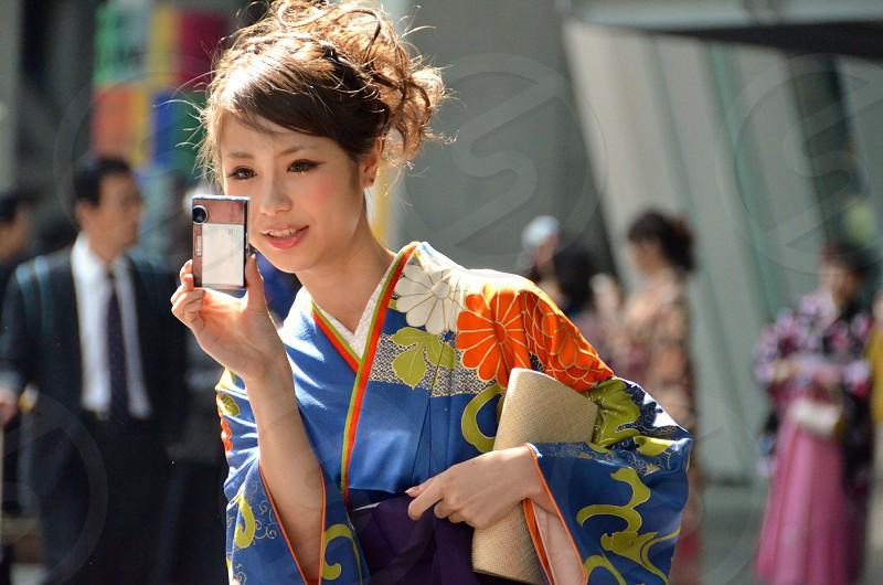 woman wearing orange and blue kimono holding camera photo