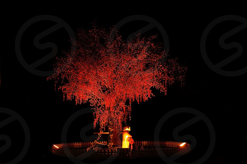 red chinese new year tree with small statue illuminated with red light photo