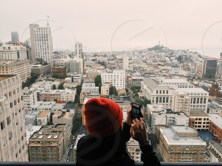 woman in black jacket taking picture of city view photo