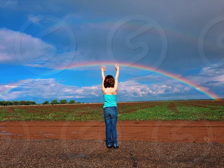 girl raising her hands on rainbow view photo
