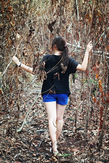 woman in black t shirt and blue shorts walking on the wither trees and grass at daytime photo