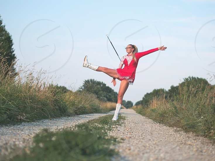 Bespectacled Blonde Teen Majorette Girl Twirling Baton Outdoors in Red Dress photo